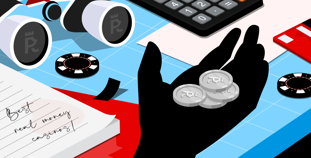A hand holding some Casinopro coins in front of a table with a note reading 'Best Real Money Casinos' along with casino chips, a calculator and a pair of binoculars